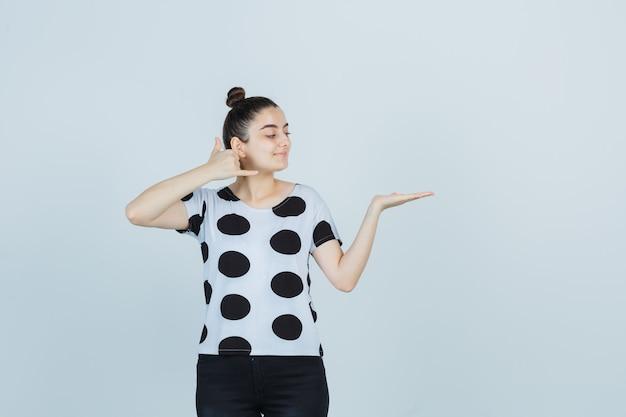 Junge dame, die telefongeste zeigt, während sie vorgibt, etwas im t-shirt, in den jeans zu halten und freudig, vorderansicht zu schauen.
