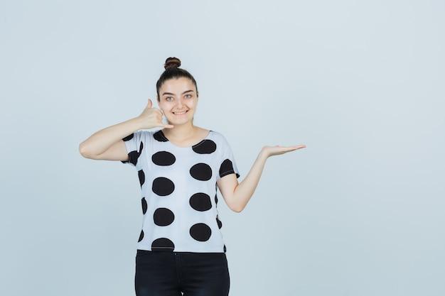 Junge dame, die telefongeste zeigt, während sie vorgibt, etwas in t-shirt, jeans zu halten und glücklich auszusehen. vorderansicht.