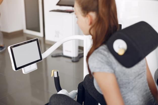 Junge dame, die übungen auf simulator im phisiotherapieraum macht