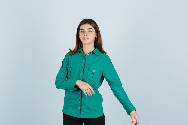 Junge dame, die vorgibt, etwas auf ihrer linken seite im grünen hemd zu zeigen und verwirrt aussieht. vorderansicht.