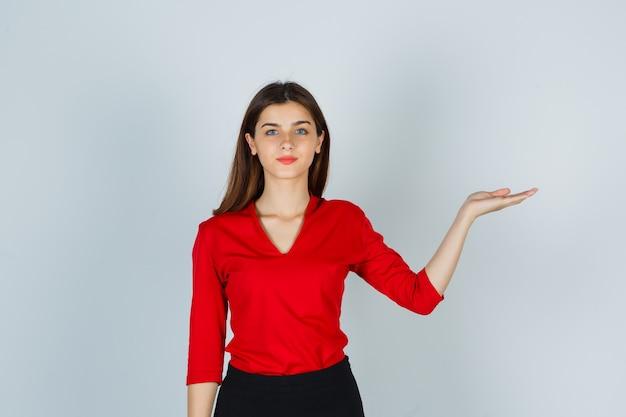 Junge dame, die vorgibt, etwas in roter bluse, rock und selbstbewusstsein zu halten