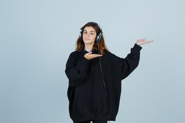 Junge dame, die vorgibt, etwas zu zeigen, während sie musik mit kopfhörern in übergroßem kapuzenpulli, hosen hört und selbstbewusst aussieht. vorderansicht.