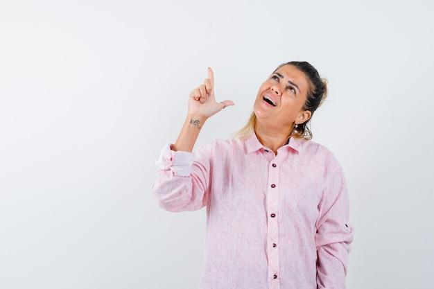 Junge dame, die waffengeste im rosa hemd zeigt und fröhlich schaut