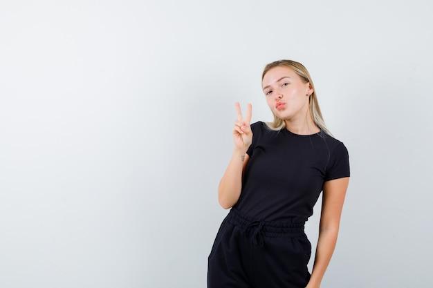 Junge dame, die wange auf finger in t-shirt, hose und fröhlich aussehend, vorderansicht lehnt.