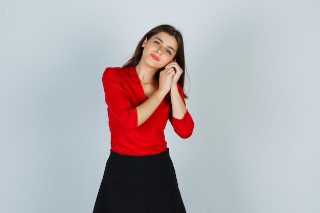 Junge dame, die wange auf hände in roter bluse, rock und niedlich aussehend lehnt