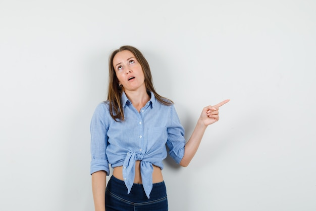 Junge dame, die weg zeigt, während sie im blauen hemd, in der hose und im gereizten blick aufschaut.