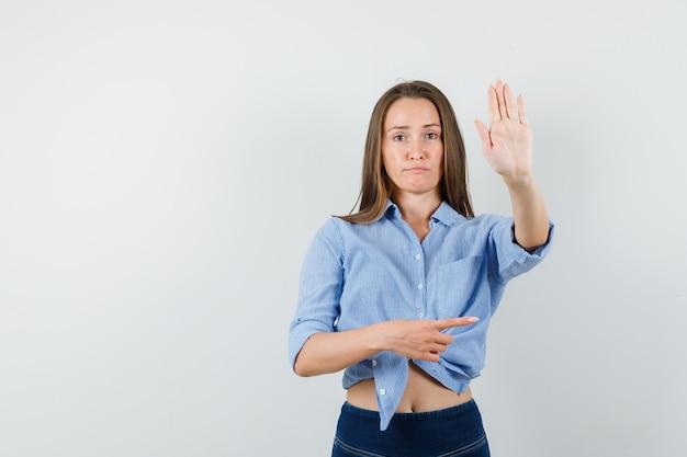 Junge dame, die zur seite zeigt und stoppgeste im blauen hemd zeigt