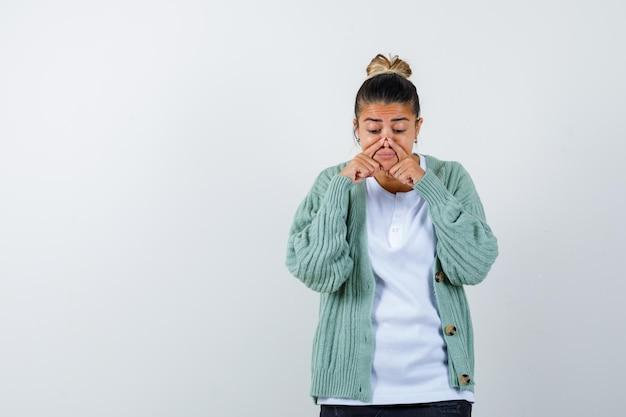 Junge dame drückt die nase mit den fingern in t-shirt, jacke und sieht lustig aus