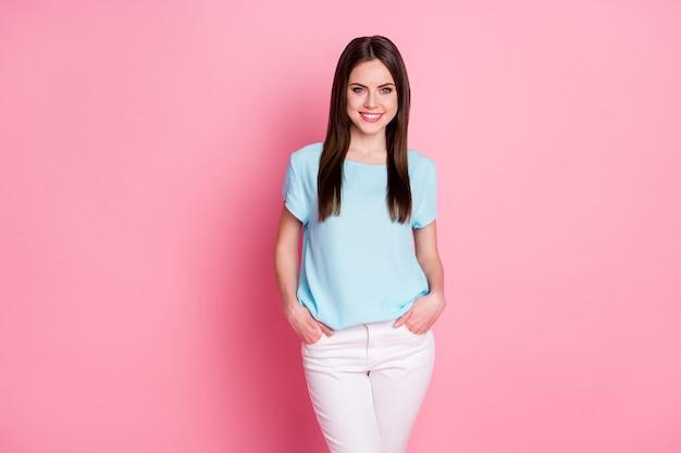 Junge dame fröhlich gute laune tragen lässiges blaues t-shirt weiße hose isoliert rosa pastellfarbenen hintergrund