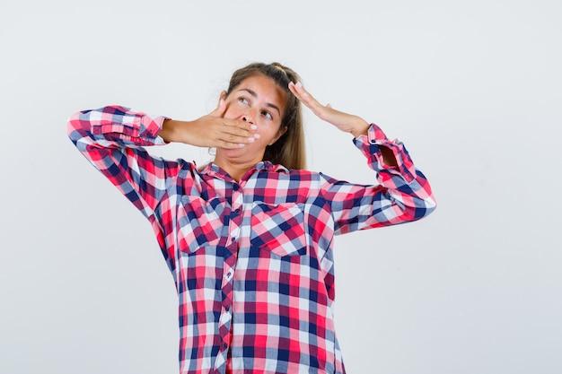 Junge dame gähnt, während sie den oberkörper im karierten hemd streckt und entspannt aussieht. vorderansicht.