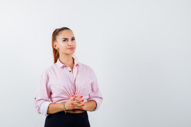Junge dame hält gefaltete finger vor sich in hemd, hose und sieht nachdenklich aus, vorderansicht.
