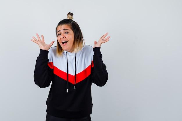 Junge dame hebt gespreizte handflächen im hoodie-pullover und sieht verängstigt aus