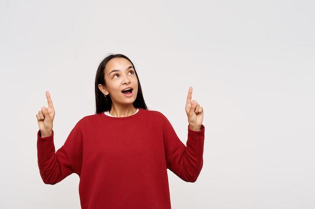 Junge dame, hübsche asiatin mit dunklen langen haaren. sie trägt einen roten pullover und zeigt nach oben, wundert sich über das, was sie sieht. aufpassen am kopienraum, isoliert, auf weißem hintergrund