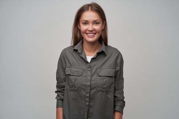 Junge dame, hübsche frau mit braunen langen haaren. graues hemd tragen und lächeln. sie stellt sich selbst vor. selbstbewusste haltung. auf grauem hintergrund isoliert in die kamera schauen