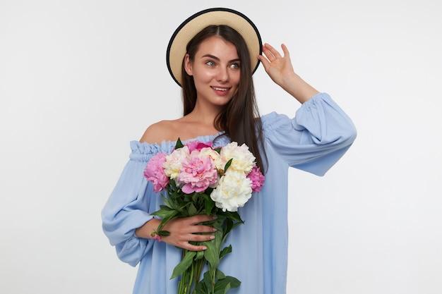 Junge dame, hübsche frau mit langen brünetten haaren. tragen eines hutes und eines blauen kleides. hält einen blumenstrauß in der hand und berührt ihren hut. beobachten sie rechts den kopierbereich über der weißen wand