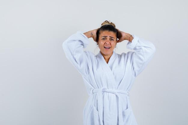 Junge dame im bademantel, die hände hinter dem kopf hält und verwirrt aussieht looking