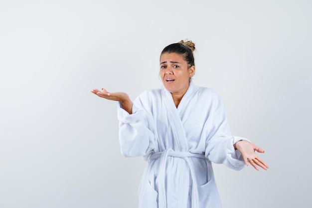 Junge dame im bademantel streckt die hand in fragender geste und sieht unzufrieden aus