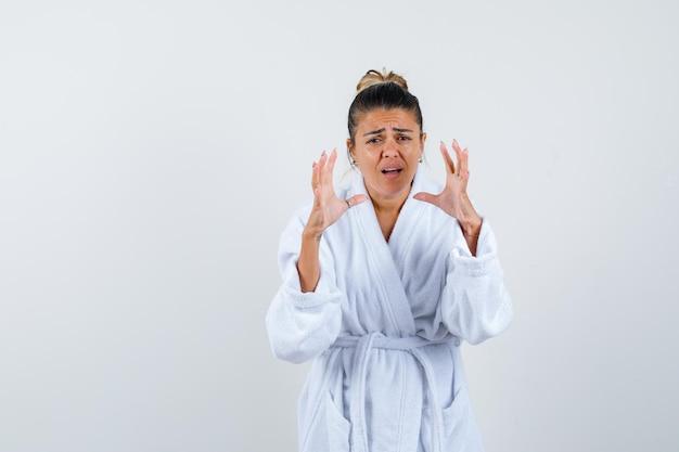 Junge dame im bademantel streckt die hand in fragender geste und sieht verwirrt aus