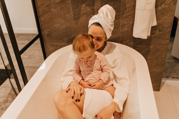 Junge dame im bademantel und im handtuch liegend im badezimmer. süßes kind sitzt auf mutter und spielt.