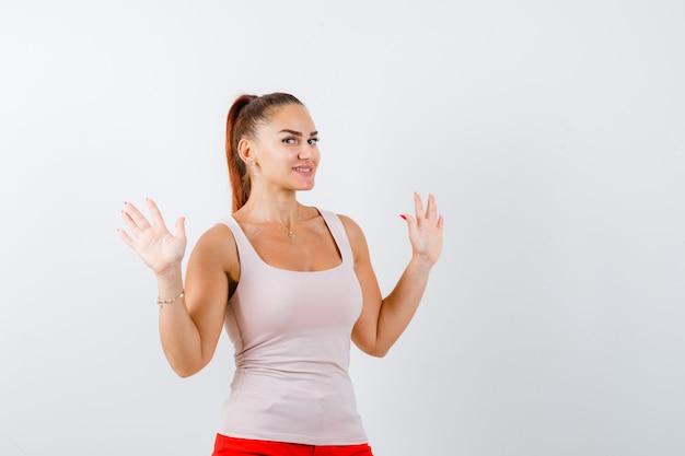 Junge dame im beige trägershirt zeigt nummer zehn und schaut fröhlich, vorderansicht.