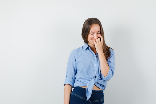 Junge dame im blauen hemd, hosen, die hand auf gesicht halten und freudig schauen