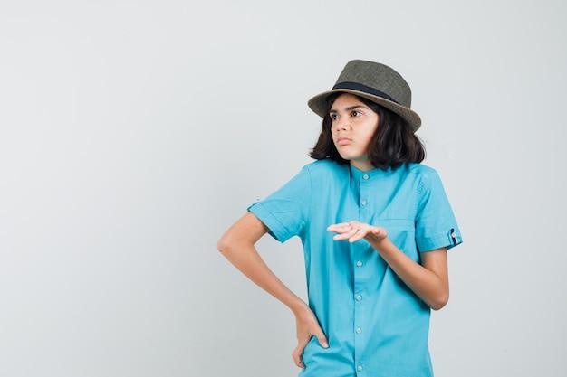 Junge dame im blauen hemd, hut, der hand mit aggressiver weise hebt und nervös schaut