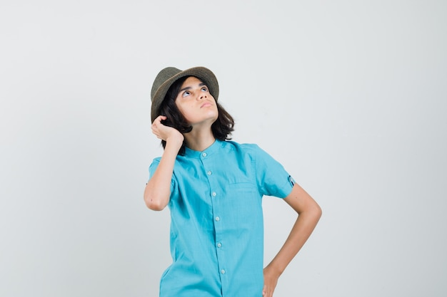 Junge dame im blauen hemd, hut, der himmel betrachtet