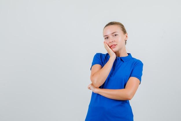Junge dame im blauen t-shirt, die wange auf erhobene handfläche lehnt und fröhlich aussieht