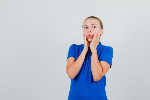 Junge dame im blauen t-shirt schaut weg mit den händen auf der wange