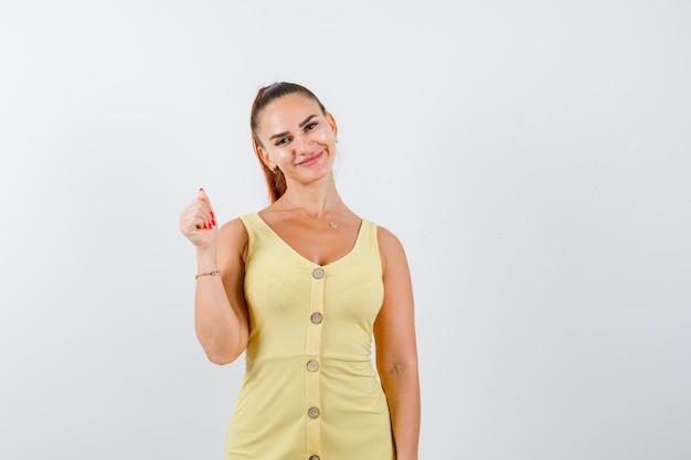 Junge dame im gelben kleid, das aufwirft, während hand hebt und lustig, vorderansicht schaut.