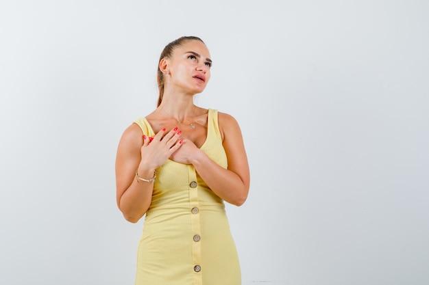 Junge dame im gelben kleid, das hände auf brust hält und nachdenklich, vorderansicht schaut.