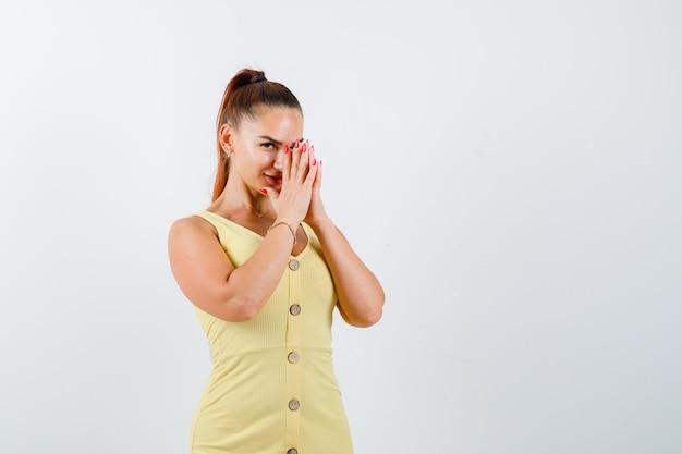 Junge dame im gelben kleid drückt hände zusammen und schaut neugierig, vorderansicht.