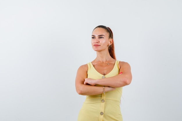 Junge dame im gelben kleid hält arme verschränkt, schaut weg und schaut nachdenklich, vorderansicht.