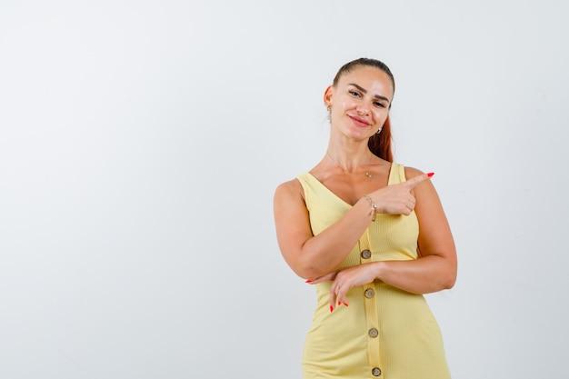 Junge dame im gelben kleid zeigt auf die obere rechte ecke und schaut fröhlich, vorderansicht.