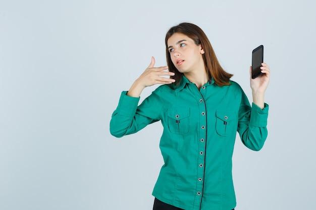 Junge dame im grünen hemd, das auf handy zeigt und verwirrt, vorderansicht schaut.