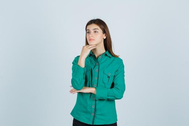 Junge dame im grünen hemd, das hand unter kinn hält und nachdenklich, vorderansicht schaut.