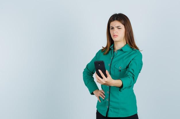 Junge dame im grünen hemd, das handy betrachtet und verwirrt, vorderansicht schaut.