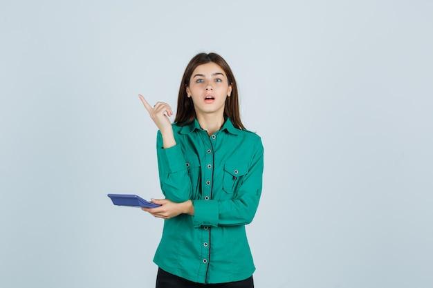 Junge dame im grünen hemd, das taschenrechner hält, während eureka-geste zeigt, nach oben zeigt und überrascht schaut, vorderansicht.