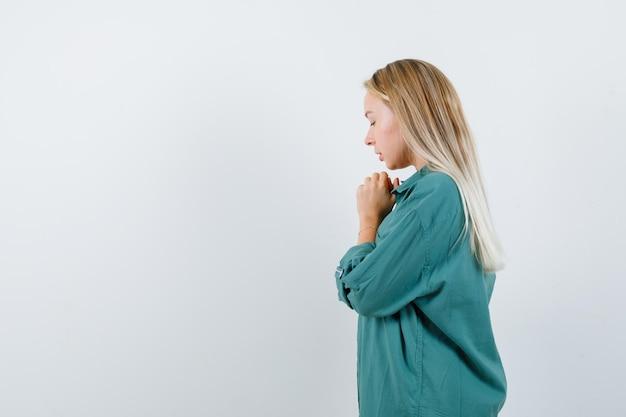 Junge dame im grünen hemd, die beim beten die hände gefaltet hält und hoffnungsvoll aussieht.