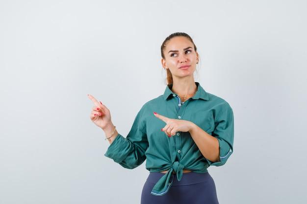 Junge dame im grünen hemd, die beiseite zeigt und nachdenklich aussieht, vorderansicht.