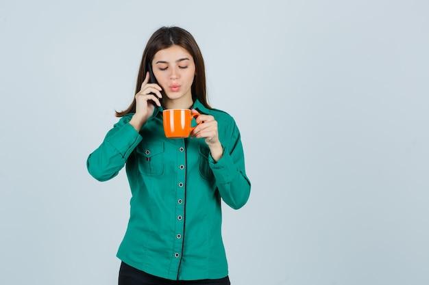 Junge dame im hemd, die orange tasse tee hält, auf dem handy spricht und zuversichtlich schaut, vorderansicht.