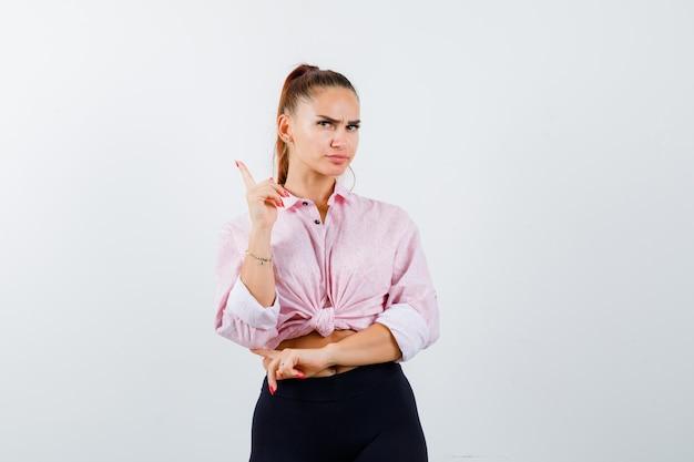 Junge dame im hemd, hose zeigt nach oben, hat ausgezeichnete idee oder lösung und sieht klug aus, vorderansicht.