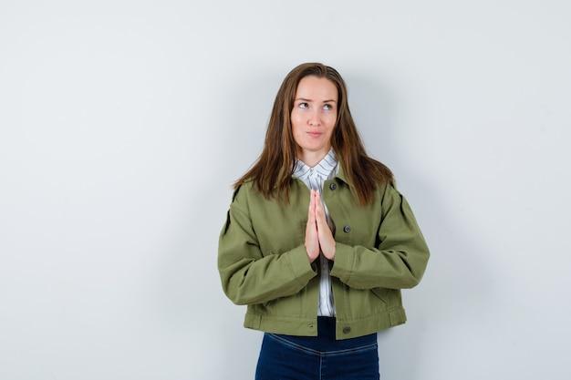 Junge dame im hemd, jacke, die namaste-geste zeigt und verträumt aussieht, vorderansicht.