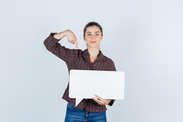 Junge dame im hemd, jeans nach unten zeigend, papierposter haltend und selbstbewusst aussehend, vorderansicht.
