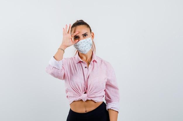 Junge dame im hemd, maske, die auge mit den fingern öffnet und konzentriert schaut