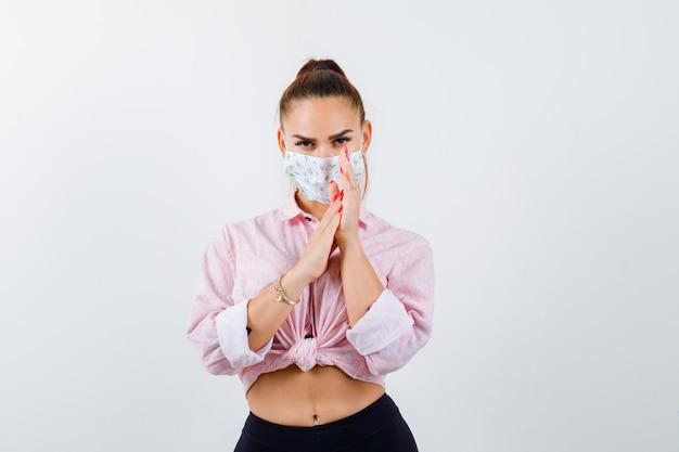 Junge dame im hemd, maske, die handflächen aneinander reibt und vernünftig aussieht, vorderansicht.