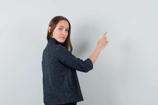 Junge dame im hemd zeigt nach oben, während sie nach vorne schaut und vernünftige rückansicht schaut