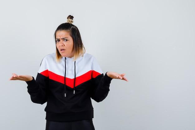 Junge dame im hoodie-pullover, die hände in fragender geste ausdehnt und ernst schaut