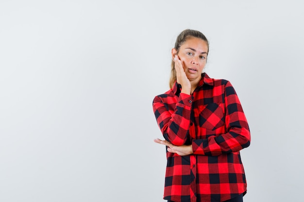 Junge dame im karierten hemd berührt haut auf ihrer wange und sieht anmutig aus