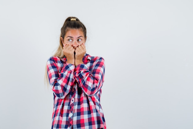 Junge dame im karierten hemd, das fäuste auf mund hält und ängstlich schaut, vorderansicht.